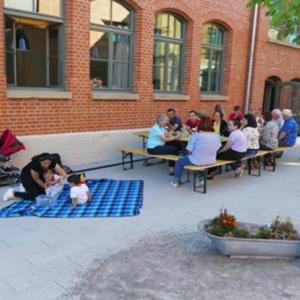 """Das Foto zeigt eine Gruppe Menschen an einem Tisch und links danben eine Frau mit zwei Kindern auf einer Decke. Die Veranstaltung gehört zum Projekt """"Fit im Kopf"""" in Neckarweihingen."""
