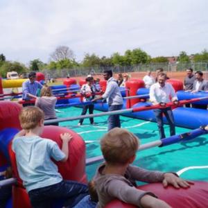 Das Foto zeigt einen menschengroßen Kicker in Poppenweiler. Die Figuren werden von echten Menschen gespielt. Um das aufgeblasene Spielfeld steht Publikum.
