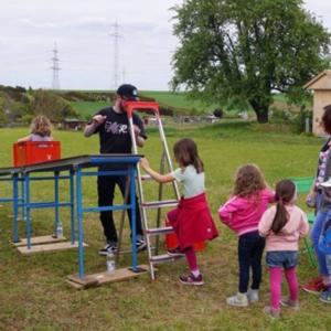 Das Bild zeigt eine Kistenrutsche für Kinder in Poppenweiler auf einer Wiese.