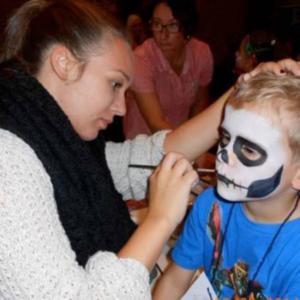Das Foto zeigt eine Frau die einen Jungen schminkt beim Kinderfasching in Poppenweiler.