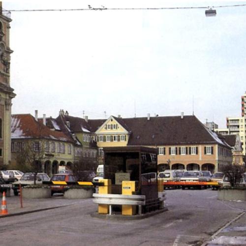 Das Foto zeigt den Markplatz in der Innenstadt in seinem früheren Zustand. Ein Parkplatz befindet sich auf dem Platz.