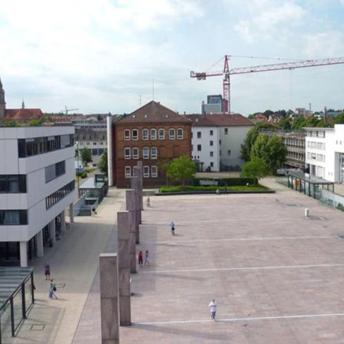 Das Foto zeigt den neuen Rathausplatz nach dem Umbau. Abriss und Neubau von Gebäuden sind zu vermerken. Auf dem Platz befinden sich sechs Betonstelen. Unter dem Platz ist eine Tiefgarage zu finden.