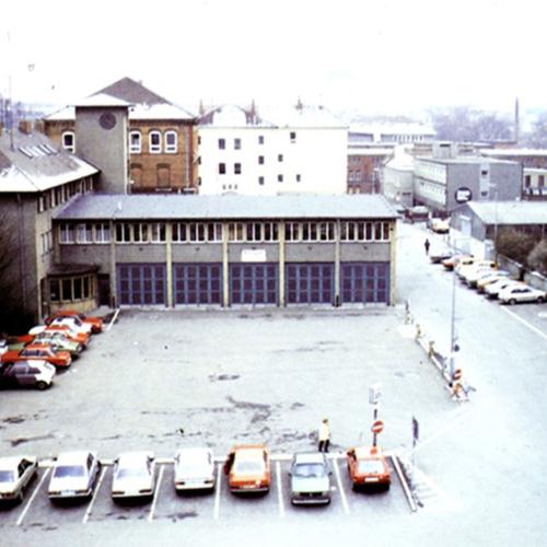 Das Foto zeigt den damaligen Rathausplatz. Ein Platz ist umrundet von Parkplätzen.