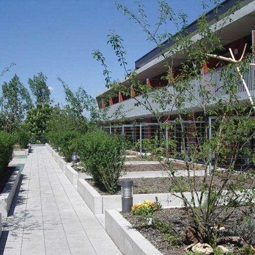 Man blickt auf die Terrassen des Wohn- und Geschäftshauses. Es sind Beete mit etwas Bepflanzung zu sehen.